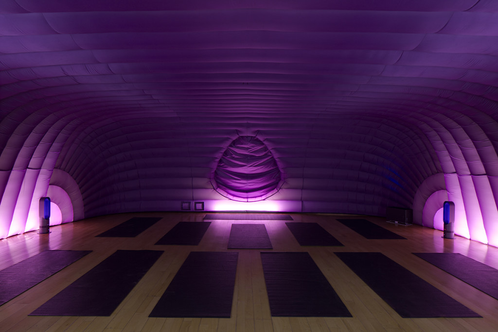 The image shows the pod of hotpod yoga, a purple inflatable room filled with yoga mats and lit at the sides.