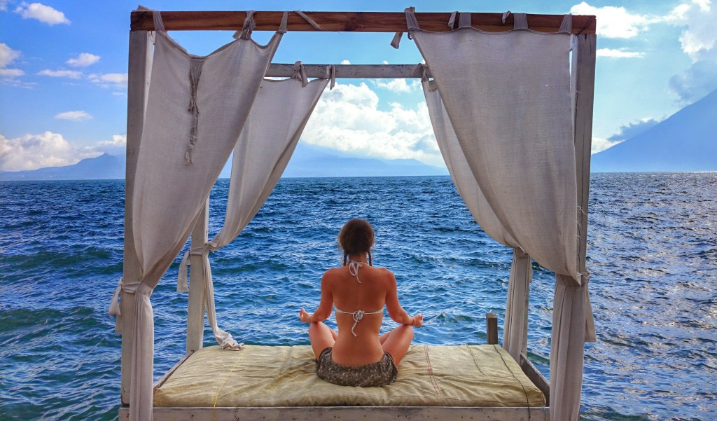 Image shows Jade sitting on a four poster bed cross legged and meditating, looking out towards the sea.