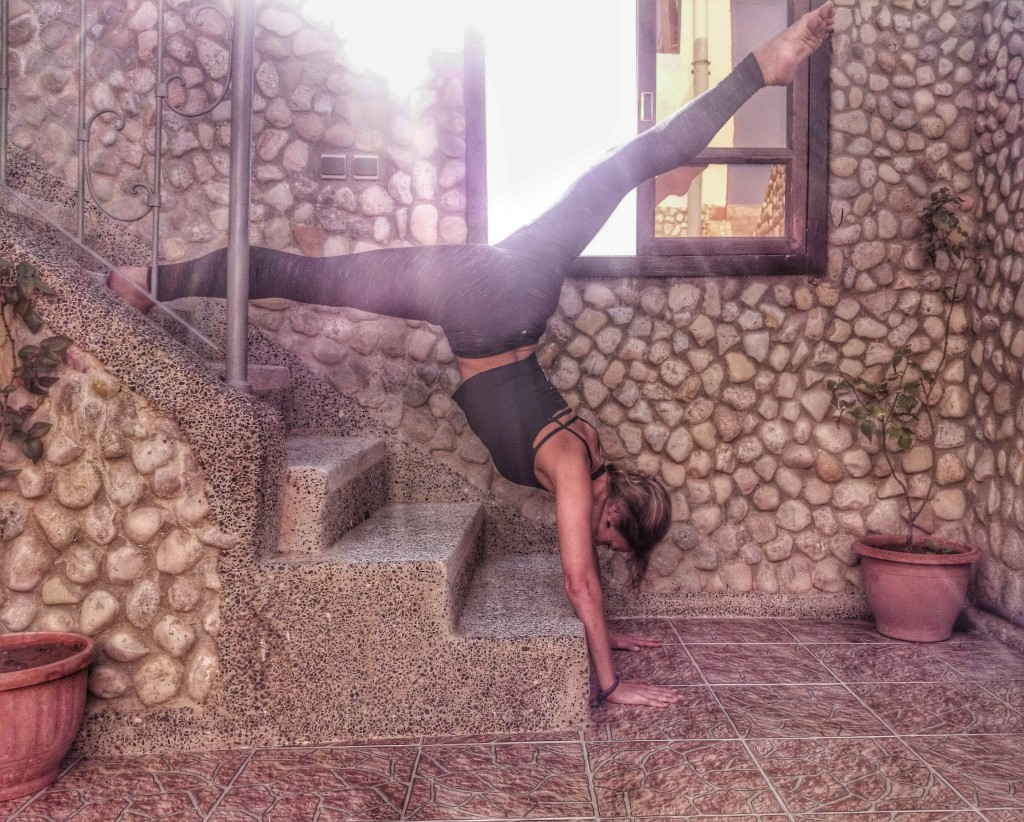 Image shows Jade practising handstands on the steps in Morocco to demonstrate how yoga makes you strong.