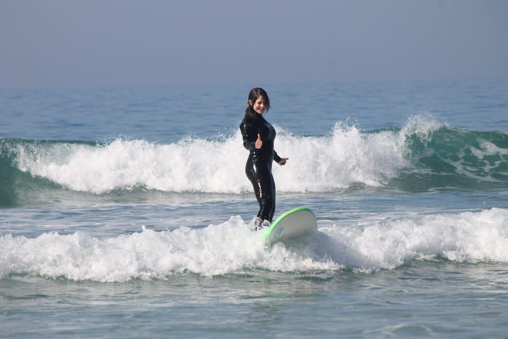 Girl surfing with thumbs up