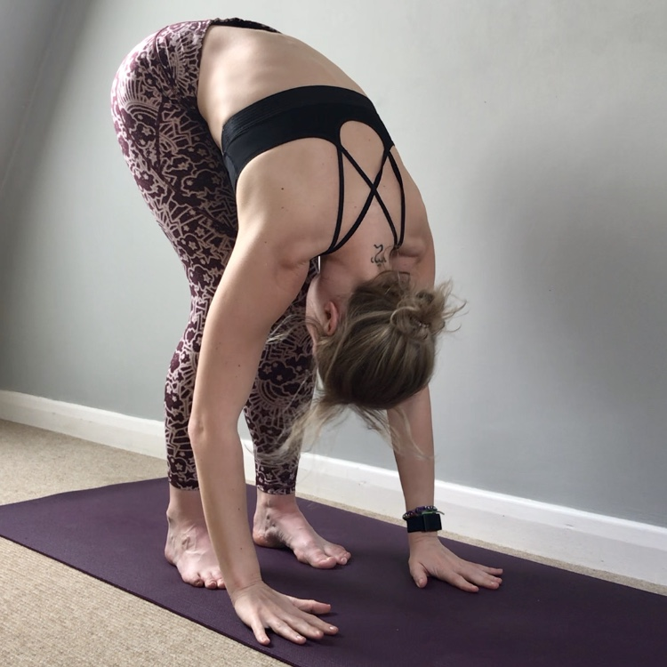Photograph of Jade doing yoga at home in a in standing forward fold, uttanasana.