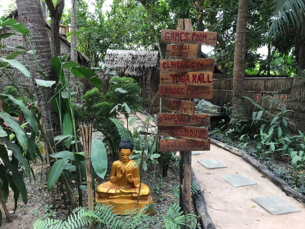 Signs pointing to yoga hall and other facilities at Hariharalaya Retreat Centre.